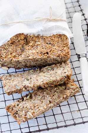 multi grain: Multi grain seeded wholemeal bread with nuts, pumpkin, sunflower, sesame, flax seeds and almonds wrapped in muslin cloth on a cooling rack
