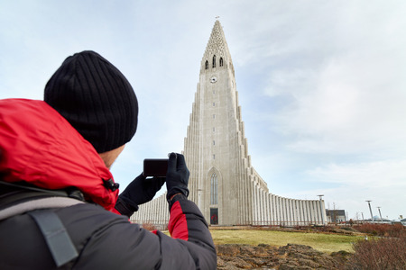 mochila de viaje: rear view adventure travel backpack man taking pictures of the Hallgrimskirkja cathedral in reykjavik iceland Foto de archivo