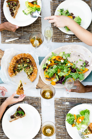 entertaining: Overhead view of group of friends, hands serving up fresh organic platters of food laid out on a table, a casual outdoor dining party setting