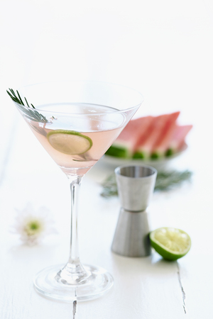 arrangment: Light pink cocktail mocktail in a martini glass decorated with a slice of lime and garnish with a slice of watermelon and flowers in the background