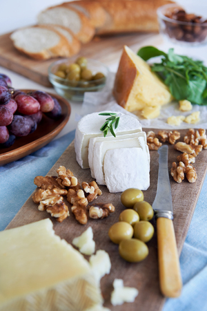 goat cheese: Cheese platter starter appetiser pre dinner snack, assortment of different cheeses, nuts, olives and grapes Stock Photo