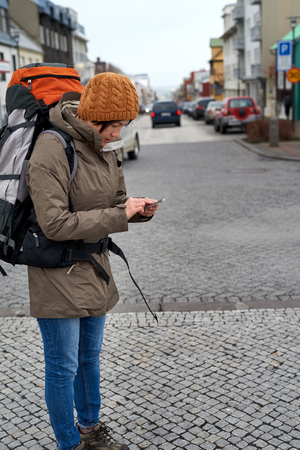 lost city: Young Asian backpacker tourist woman in rain jacket and beanie busy with her mobile Phone middle of urban city street