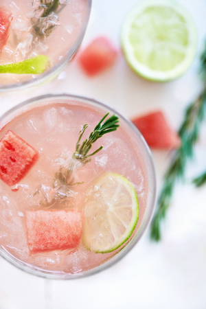 garnish: Close up of a delicious pink girly feminine cocktail mocktail drink with slices of watermelon, lime and rosemary