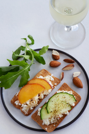 melba: Party canapes snacks ricotta cottage cheese with sliced nectarine and cucumber and a glass of wine