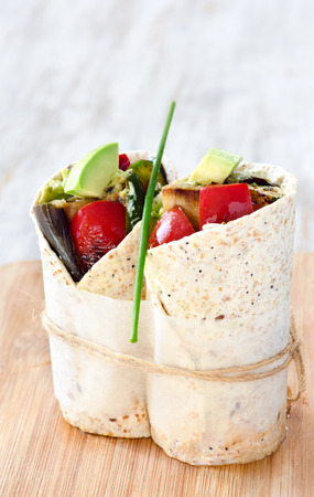 eggplants: Healthy vegetarian vegan tortilla wraps with roasted vegetables like aubergine eggplant, red bell peppers, avocado Stock Photo