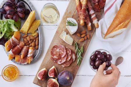 Hände immer eine Olive, Wurst Wurstauswahl Salami, Chorizo, Schinken umwickelt Brot-Sticks mit frischen Feigen, Honigmelone, Mandeln und weißen Wein Standard-Bild - 44451965