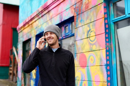 beanie: young happy caucasian adult man wearing beanie hat talking on mobile cell phone. Stock Photo