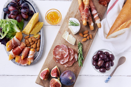 Cheese and cured meat charcuterie selection salami, chorizo, prosciutto wrapped bread sticks with fresh fig, rockmelon, almonds and white wine