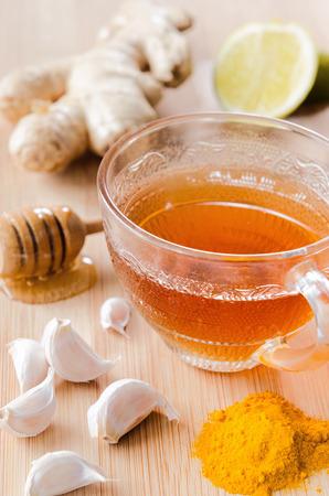 生姜、レモン、蜂蜜、ニンニク、スパイシーなデトックスド リンクのターメリックとお茶のカップ 写真素材