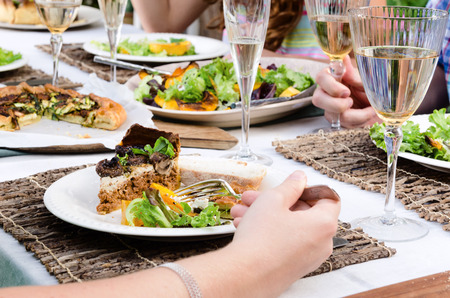 woman eat: Hand and party food on beautifully set table, healthy salad and tart for lunch garden party