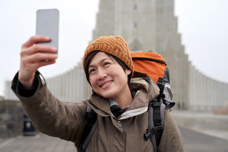 winter vacation: Happy travelling tourist Asian Chinese woman taking selfie in front of the Hallgrimskirkja cathedral in Reykjavik Iceland