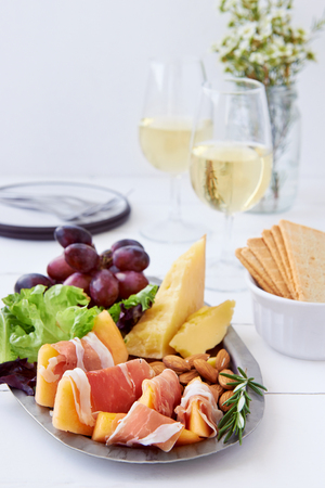 appetizers: Platter of gourmet party food, gruyere cheddar cheese with prosciutto parma ham wrapped rockmelon served with white wine