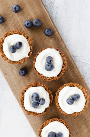 filling in: Yogurt filling in muesli shells topped with fresh blueberry, healthy dessert tart snack Stock Photo