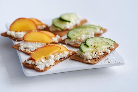 melba: Fresh cabaña ricotta aperitivo generoso plato queso merienda con melocotón en rodajas y el pepino, canapés fiesta perfecta Foto de archivo