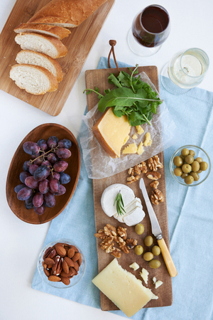 appetiser: Cheese platter starter appetiser pre dinner snack, assortment of different cheeses, nuts, olives and grapes served with wine Stock Photo