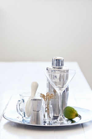 martini shaker: Silver tray with martini glass with cocktail making utensils accessories equipment shaker thimble measurer and lime garnish Stock Photo