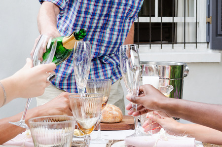 origins: Man pours champagne into glass flutes held by hands of multi racial origins, no faces