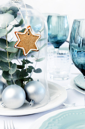 dinner party: Glass dome christmas decoration centerpiece with gingerbread star and silver bauble, white blue xmas dinner setting