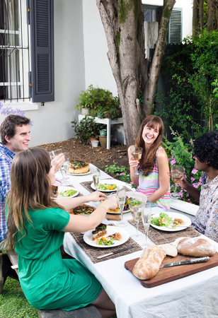 get together: Friends having fun, talking and laughing at a party with food and alcohol, a casual lunch get together in a garden