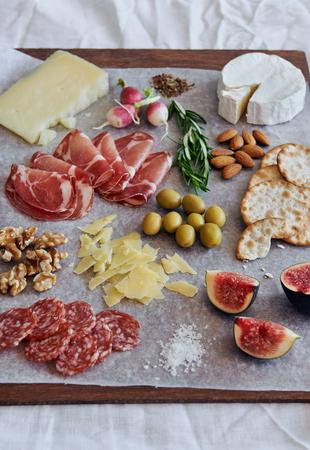charcutería: Selección de salami charcutería carne curada, coppa, con queso gruyere brie camembert servido con aceitunas galletas nueces y frutas
