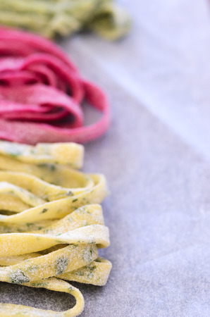 flavours: Close up of raw home hand made fresh pasta with variety of flavours, beetroot, herb, spinach Stock Photo