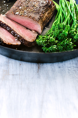 cast iron: Medium cooked steak on a cast iron pan with fresh green vegetables