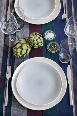 Centrepiece: Simple dinner party table place setting with natural fruit artichoke as centrepiece decoration Stock Photo
