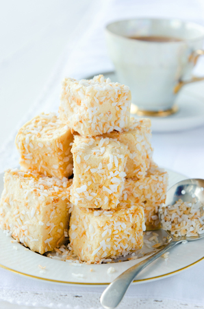 Cubes of marshmallow coated with roasted coconut bits, mini dessert treats served with tea