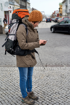 beanie: Young Asian backpacker tourist woman in rain jacket and beanie busy with her mobile Phone middle of urban city street