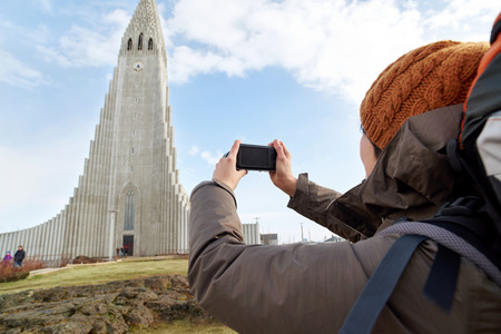 rear view of backpacker tourist travel woman taking pictures of the Hallgrimskirkja cathedral in reykjavik iceland Stock Photo