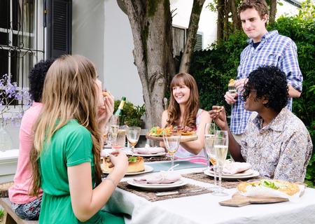 personas reunidas: Grupo de amigos que interactúan en una fiesta de jardín al aire libre, comer y beber alrededor de una mesa