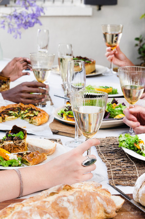 food and wine: Group of friends holding their wine glasses for a toast at a outdoor garden party with fresh organic platters of food laid out on a table, a casual party gathering Stock Photo