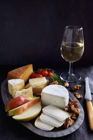 cheese platter: Dessert cheese platter with pear and nuts on dark background Stock Photo