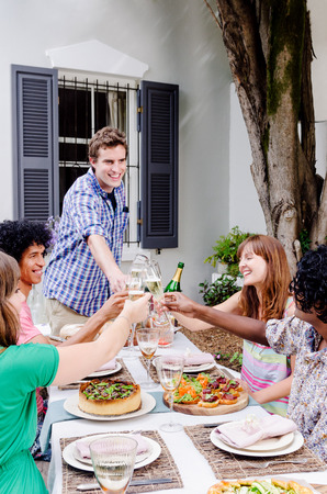 Group of multi ethnic friends having fun celebrating toasting with champagne at an outdoor garden party photo