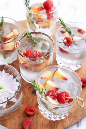 garnish: Close up of clear cocktailssoda water being served on a wooden tray decorated with flowers, raspberries, sliced apples and garnish Stock Photo