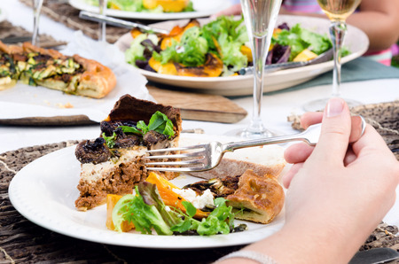 platters: Anonymous female hand holding a fork in front of a plate of food, in a a casual outdoor dining party setting with other friends and platters of food