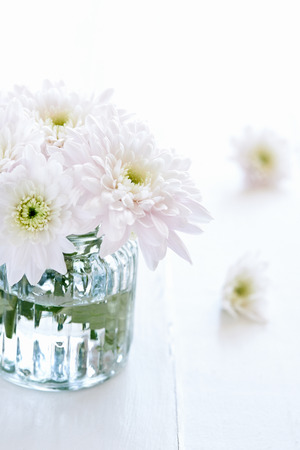 arrangment: Close up of a small arrangement of white flowers in a clear vase
