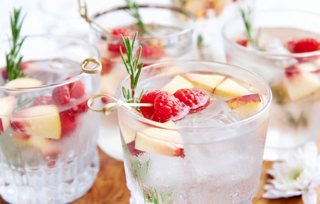 soda: Close up of clear cocktailssoda water being served on a wooden tray decorated with flowers, raspberries, sliced nectarine and rosemary garnish