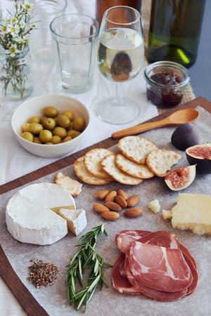 charcutería: Selección de gourmet curado salami charcutería carne, coppa, con queso gruyere brie camembert servido con aceitunas nueces y frutas