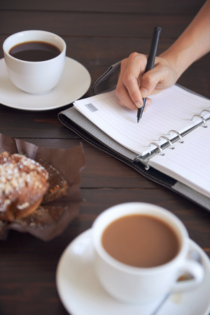 person writing: Cups of coffee with a muffin and a  person writing in her diary Stock Photo