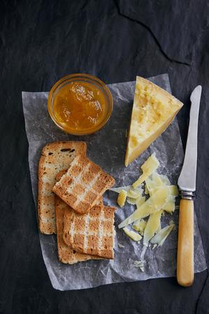 melba: Queso y galletas que se presentan en papel encerado y pizarra con mermelada