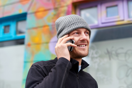 young adult man: young happy caucasian adult man wearing beanie hat talking on mobile cell phone. Stock Photo