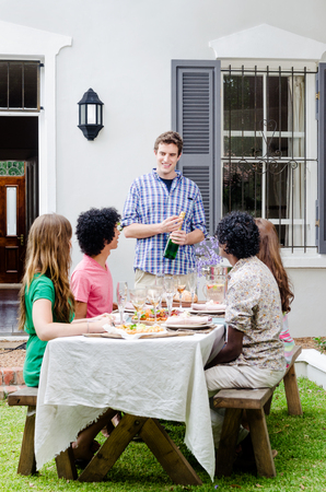 Group of friends having a gathering party, celebrating a special occasion with speech and champagne, sitting around a table with plenty of food photo