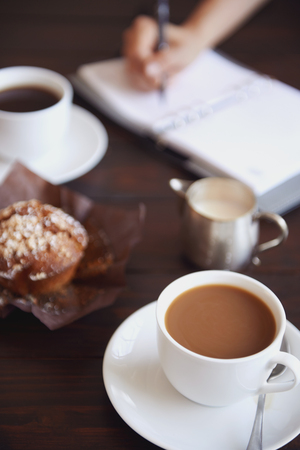 person writing: Cups of coffee with a muffin and a  person writing in her daily planner in the background