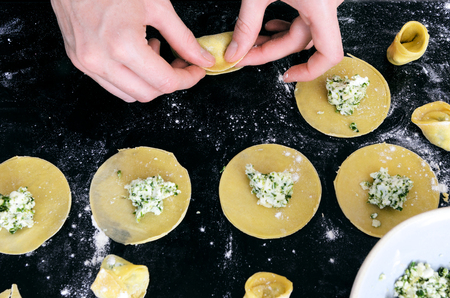 Pair of hands filling tortellini or ravioli with ricotta and spinach herb stuffing , from overhead view Banque d'images