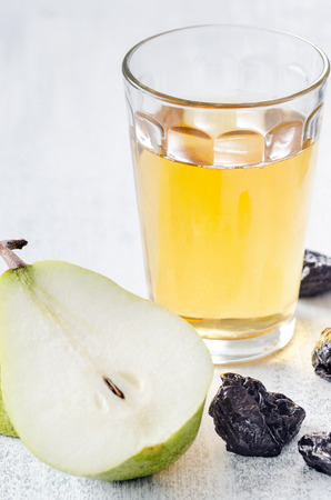 digestion: Glass of apple juice with pear and dried prunes for a healthy detox meal to aid digestion