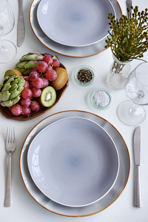 domestic life: Simple elegant dinner table setting crockery cutlery and glasses, using fresh fruit and vegetable kiwi grapes artichoke as centrepiece decoration Stock Photo