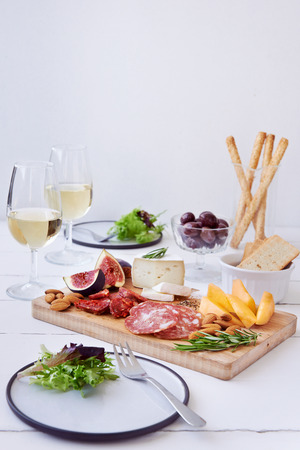 food and wine: Cheese and charcuterie pairing, chorizo salami, served with fresh fruit rockmelon, fig with olives, salad and white wine Stock Photo