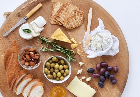 queso de cabra: Selecci�n Gourmet de quesos, queso cheddar fresco gouda queso ricotta brie de cabra, aceitunas con nueces uvas galletas y pan, servido en una tabla de madera grande Foto de archivo