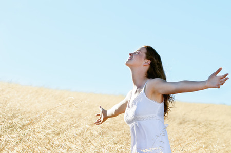 outstretch: Young carefree woman stands in field with arms outstretch, welcoming summer and sunshine